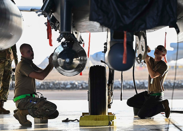 Two U.S. Air Force F-15E Strike Eagle dedicated crew chiefs assigned to the 380th Expeditionary Aircraft Maintenance Squadron (EAMXS) perform maintenance on an F-15E at Al Dhafra Air Base, United Arab Emirates, Jan. 19, 2021.