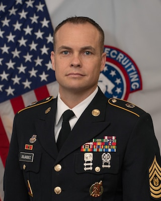 Command photo of CSM Dojaquez in his Army Service Uniform in front of the American Flag and the BN Colors.