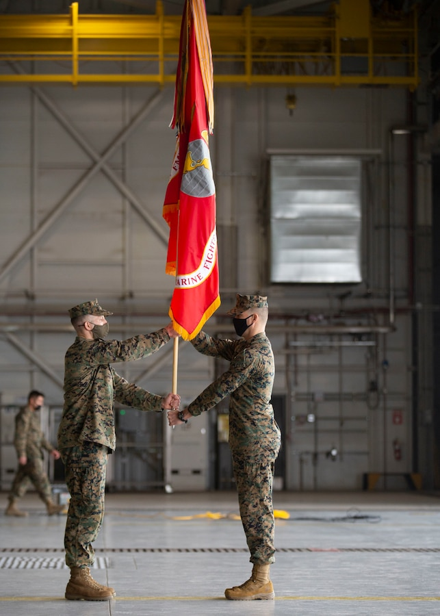 U.S. Marine Corps Lt. Col. Alexander Goodno, the incoming commanding officer, left, and Sgt. Maj. Collin Barry, the incoming sergeant major, with Marine Fighter Attack Squadron (VMFA) 225, Marine Aircraft Group 13, 3rd Marine Aircraft Wing, exchange the organizational colors during the re-designation and assumption of command ceremony at Marine Corps Air Station Yuma, Ariz., Jan. 29, 2021. The ceremony official re-designated Marine All-Weather Fighter Attack Squadron (VMFA(AW) 225 to VMFA-225, signifying the squadron's transition from the AV-8B Harrier to the F-35B Lightning II. (U.S. Marine Corps photo by Lance Cpl. Juan Anaya)