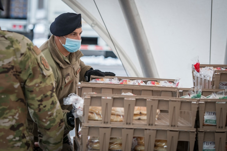 U.S. Air Force Master Sgt. Ian McMahon, 103rd Security Forces Squadron, organizes bread trays for distribution at Rentschler Field in East Hartford, Connecticut, Feb. 4, 2021. Airmen from the Connecticut National Guard's 103rd Airlift Wing are supporting logistics operations at Foodshare's drive-thru emergency distribution site here, which has distributed over 8,000,000 pounds of food to 233,000 cars since April 20, 2020. (U.S. Air National Guard photo by Staff Sgt. Steven Tucker)