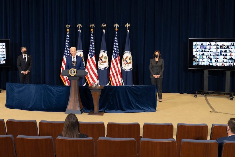 A man stands on a stage at a lectern with microphones with two people socially distanced on either side of him. Four flags are in the background and the audience is socially distanced.