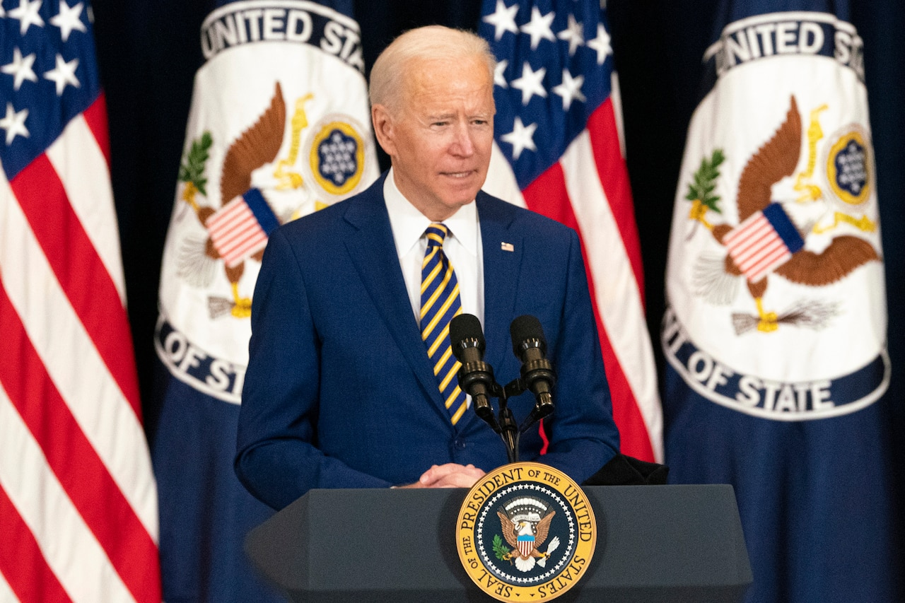 A man stands at a lectern with microphones and the Seal of the President of the United States affixed to the lectern. Four flags are in the background.