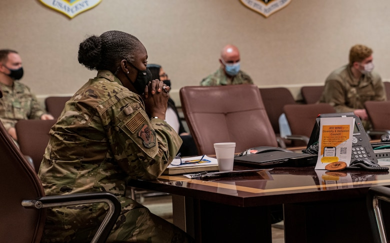 Chief Master Sgt. Michelle Browning, 432nd Wing/432nd Air Expeditionary Wing command chief clasps her hands as she listens to members of the Diversity and Inclusion Council