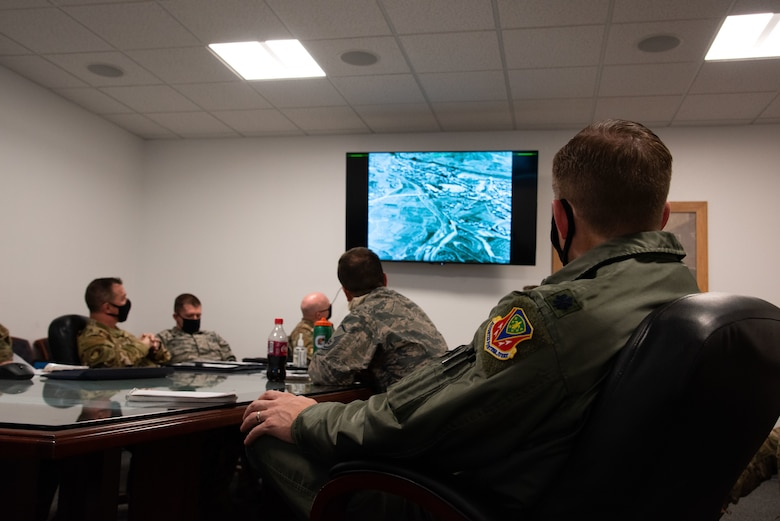 Airmen sit in a room and look at a screen. They are sitting in on a virtual staff ride.