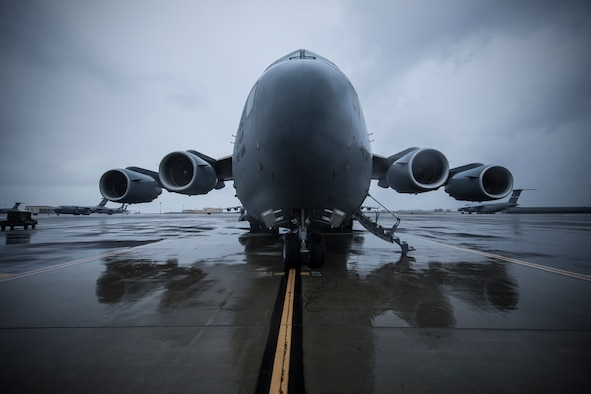 A C-17 sits on a wet flight line.