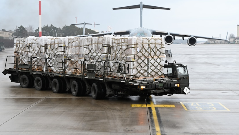 A vehicle with a long bed is carrying a few pallets on a wet flight line.
