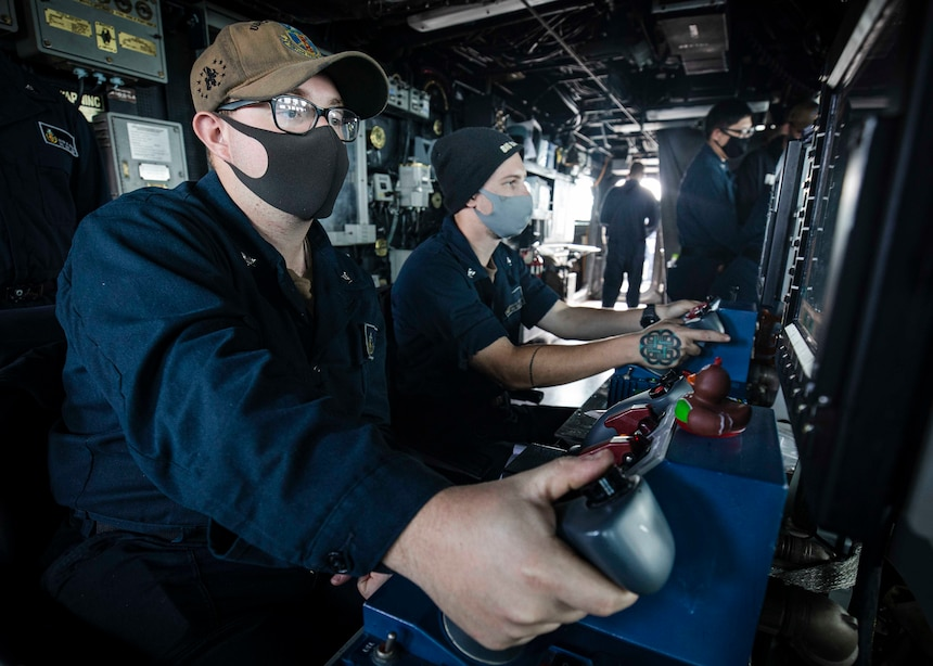 PARACEL ISLANDS, SOUTH CHINA SEA (Feb. 05, 2021) Gunner's Mate 3rd Class Carter Musgrave, left, from Zanesville, Ohio, and Gunner's Mate 3rd Class Brayden Barthel, from Hagerstown, Md., track surface contacts through mark-38 25mm gun remote operator consoles in the pilot house aboard the Arleigh Burke-class guided-missile destroyer USS John S. McCain (DDG 56) as the ship conducts routine underway operations. McCain is forward-deployed to the U.S. 7th Fleet area of operations in support of security and stability in the Indo-Pacific region. (U.S. Navy photo by Mass Communication Specialist 2nd Class Markus Castaneda)