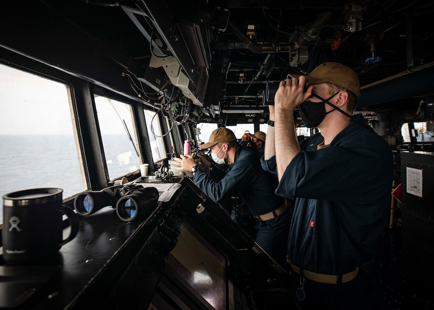 PARACEL ISLANDS, SOUTH CHINA SEA (Feb. 05, 2021) Ensign Grayson Sigler, right, from Corpus Christi, Texas, scans the horizon as Ensign Luke Dionne, from Binghamton, N.Y., looks through a telescopic alidade while standing watch in the pilot house aboard the Arleigh Burke-class guided-missile destroyer USS John S. McCain (DDG 56) as the ship conducts routine underway operations. McCain is forward-deployed to the U.S. 7th Fleet area of operations in support of security and stability in the Indo-Pacific region. (U.S. Navy photo by Mass Communication Specialist 2nd Class Markus Castaneda)