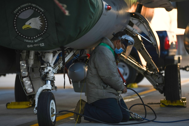 U.S. Air Force Airman 1st Class Alex Peguero, 31st Aircraft Maintenance Squadron assistant dedicated crew chief, services a tire of an F-16 Fighting Falcon at Aviano Air Base, Italy, Feb. 1, 2021. Crew chiefs routinely inspect and service the aircraft to ensure mission and operational readiness. (U.S. Air Force photo by Senior Airman Ericka A. Woolever).