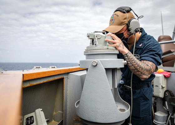 Boatswain's Mate 3rd Class Zachary Kai, from Kau, Hawaii, looks through a telescopic alidade while standing watch on the bridge wing aboard the Arleigh Burke-class guided-missile destroyer USS John S. McCain (DDG 56)
