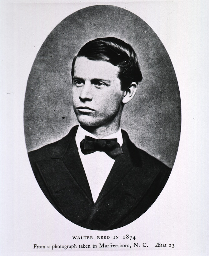 An oval photo shows a young man in a suit and bow tie.