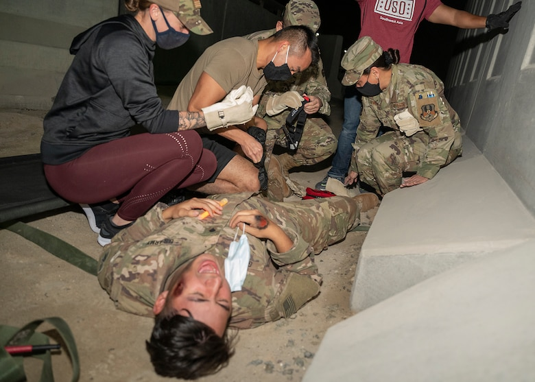 Participants in the 380th Air Expeditionary Wing Honorary Members Program perform self-aid buddy care on a U.S. Army soldier with simulated injuries during a 380th Expeditionary Medical Group (EMDG) immersion event at Al Dhafra Air Base, United Arab Emirates, Jan. 28, 2021.