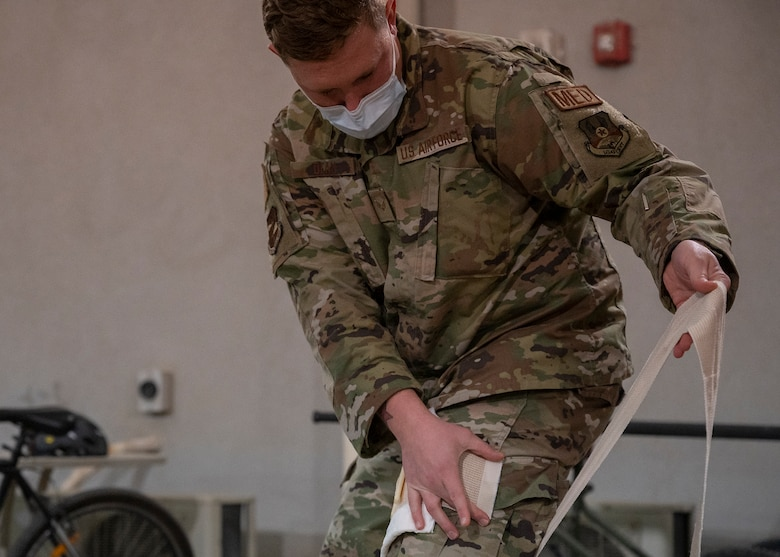 U.S. Air Force Senior Airman Kevin Dean, 380th Expeditionary Medical Group (EMDG) technician, demonstrates self-aid buddy care during a 380th EMDG immersion event at Al Dhafra Air Base, United Arab Emirates, Jan. 28, 2021.