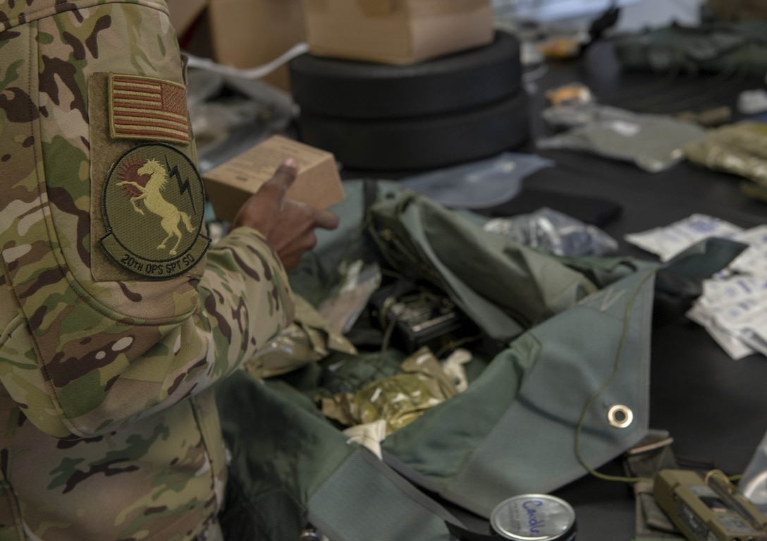 Photo of Airman packing survival kit.