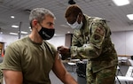 Female service member giving a COVID-19 vaccine to a male service member.