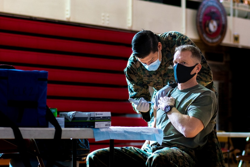 An older service member sits in a chair while a younger service member  leans down and administers the vaccine.