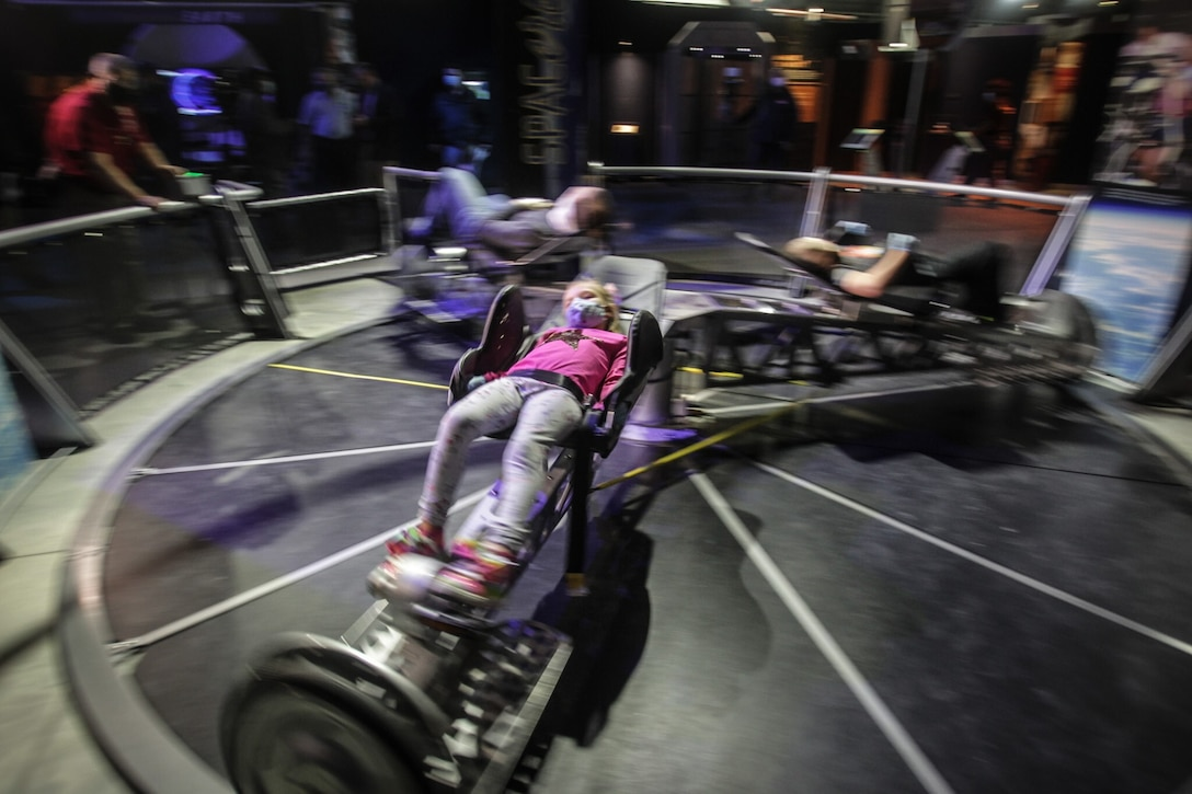 """Laney Daniel, from Englewood, rides the space bike at the National Museum of the U.S. Air Force exhibit, """"SPACE: A Journey to Our Future."""" The exhibition features: touching actual rocks from the surface of the Moon and Mars, a Mars Base Camp, habitat, work pod and a centrifuge that is powered by a bicycle along with artifacts from the space program. The exhibition will be open through Labor Day and is free to the public. JIM NOELKER/COX FIRST MEDIA STAFF"""
