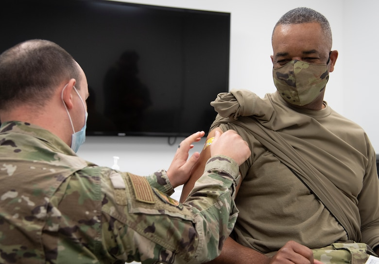 Command Chief Master Sergeant of Air Force Reserve Command Timothy C. White Jr., has a bandaid placed over where he recieved his second COVID-19 vaccine from Senior Airman Jarred Wright, an immunization technician with the 78th Medical Group, at Robins Air Force Base, Georgia, Feb. 4, 2021. The two-dose vaccines were recently approved by the Food and Drug Administration under an emergency use authorization and are currently offered to DoD personnel on a voluntary basis. (U.S. Air Force photo by Master Sgt. Stephen D. Schester)