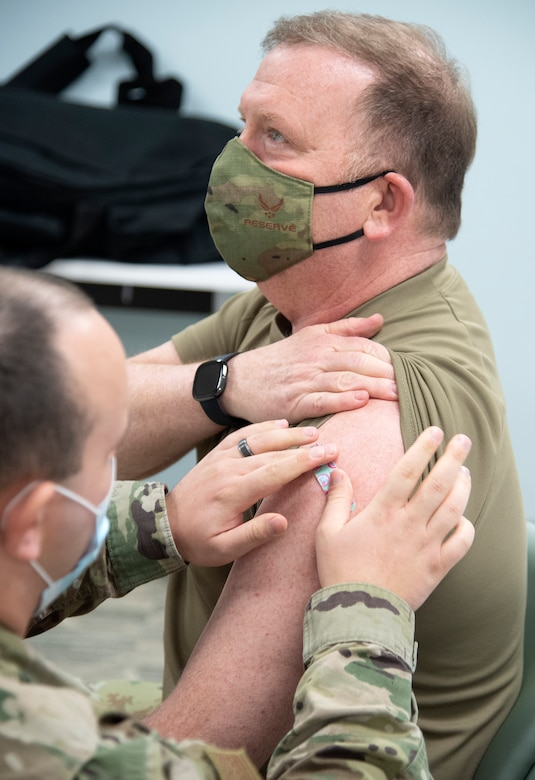 Chief of Air Force Reserve, Lt. Gen. Richard W. Scobee, has a bandaid placed over where he recived his second COVID-19 vaccine from Senior Airman Jarred Wright, an immunization technician with the 78th Medical Group, at Robins Air Force Base, Georgia, Feb. 4, 2021. The two-dose vaccines were recently approved by the Food and Drug Administration under an emergency use authorization and are currently offered to DoD personnel on a voluntary basis. (U.S. Air Force photo by Master Sgt. Stephen D. Schester)