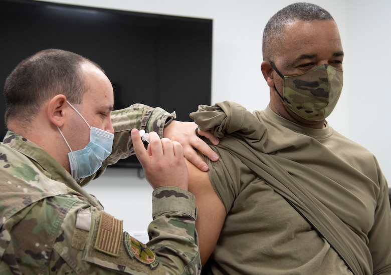 Command Chief Master Sergeant of Air Force Reserve Command Timothy C. White Jr., receives his second COVID-19 vaccine from Senior Airman Jarred Wright, an immunization technician with the 78th Medical Group, at Robins Air Force Base, Georgia, Feb. 4, 2021. The two-dose vaccines were recently approved by the Food and Drug Administration under an emergency use authorization and are currently offered to DoD personnel on a voluntary basis. (U.S. Air Force photo by Master Sgt. Stephen D. Schester)
