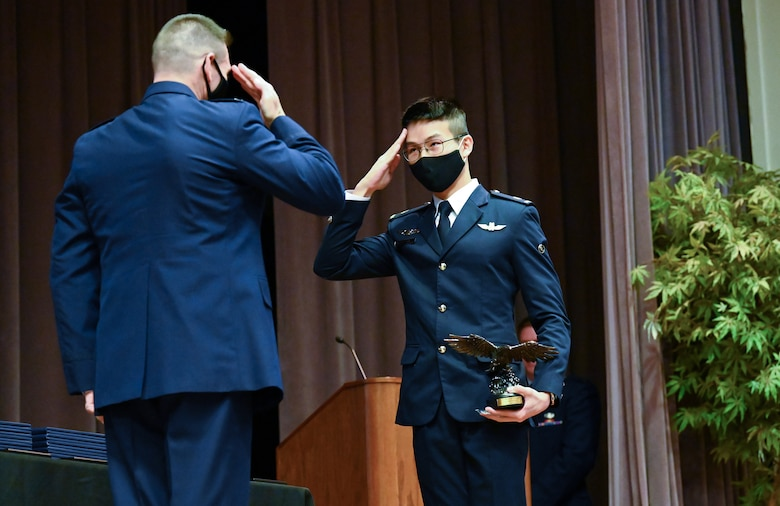 S. Air Force Col. Edward Goebel Jr., 461st Air Control Wing, commander, presents, International Student Lieutenant Tok Jing Ye of the Singapore Air Forces with the Order of Daedalians AETC Commander's Trophy and challenge coin, during the graduation ceremony, Feb. 5, 2021, on Columbus Air Force Base, Miss. The Order of Daedalians award is presented the student from each graduating class who demonstrates outstanding performance with assigned check rides, daily flying operations, as well as maintains an exceptional commander's ranking and academic score while completing specialized undergraduate pilot training. (U.S. Air Force photo by Airman 1st Class Jessica Haynie)