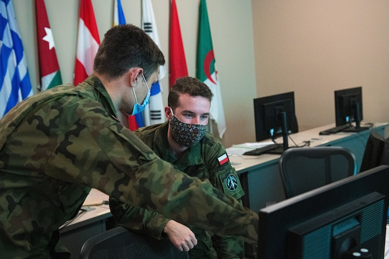 Two Polish Air Force 2nd Lts talk to each other in front of a computer