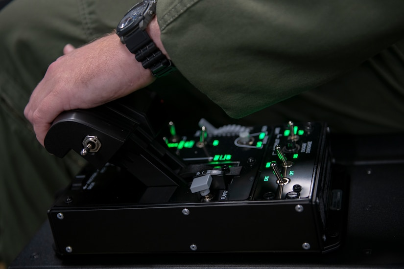 U. S. Air Force Capt. Kyle Maloney, a pilot temporarily assigned to the 559th Flying Training Squadron, pushes an immersive training device's throttle.