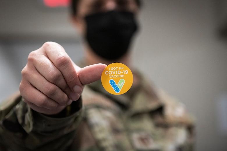 Photo of an Airman holding a sticker