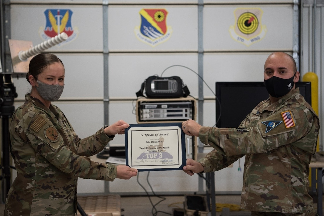 U.S. Air Force Master Sgt. Kathryn North, Falcon Top III president, left, presents the Top III Performer of the Month award for November to U.S. Space Force Sgt. Devin Witt, the 527th Space Aggressors Squadron, Space Training and Readiness Delta (Provisional) mission planning noncommissioned officer in charge, right, at Schriever Air Force Base, Feb. 3, 2021. Witt sourced 119 total force integration members for 28 electronic warfare, orbital warfare and GPS electronic attack missions to mobilize worldwide, meeting higher headquarters requirements and approvals for execution. (U.S. Space Force photo by Airman Ryan Prince)