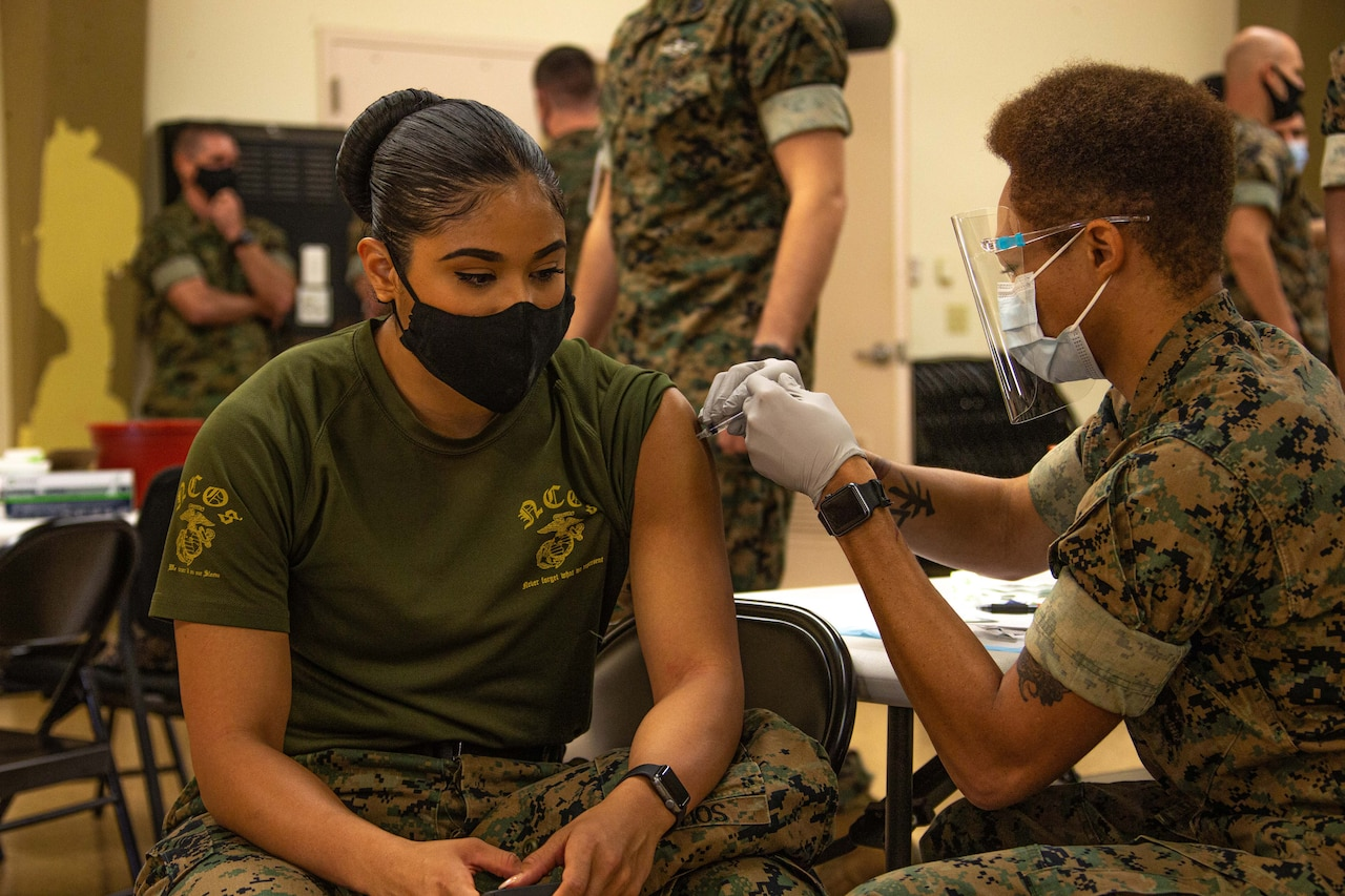 A Marine is inoculated by another service member.