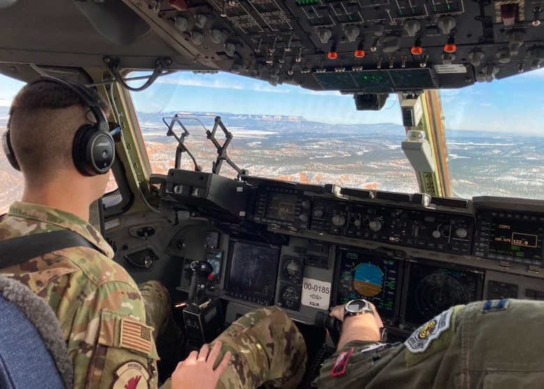 U.S. Air Force Capt. Rob Mello, left, a C-17 pilot with the 517th Airlift Squadron, and U.S. Air Force Capt. Ben Aiken, the 517th AS Weapons and Tactics Flight commander and weapons officer, prepare for a low-altitude maneuver in a U.S. Air Force C-17A Globemaster III aircraft assigned to the 176th Wing, Alaska Air National Guard, over northeastern Arizona, Jan. 9, 2021. Thirteen Airmen with the 517th AS from Joint Base Elmendorf-Richardson, Alaska, trained for a week in the southwestern U.S. with the C-17, focusing on Agile Combat Employment to train and prepare for global operations in a deployed environment.