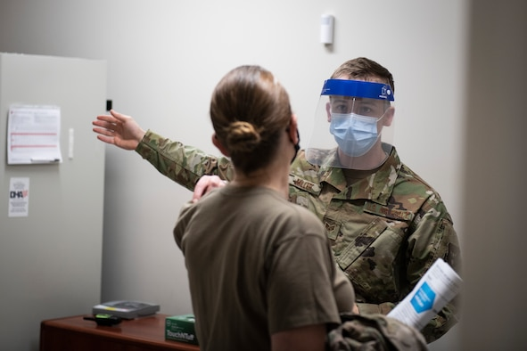 Photo of a Medical Airman directing a patient to the next station in the COVID-19 vaccination pod.