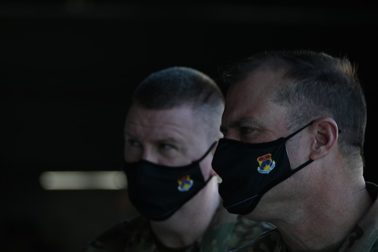 Two men in military uniforms and similar masks look intensely at an unknown source.