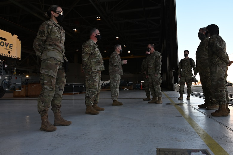 Several people in Air Force uniforms have a stare-down in an aircraft hangar.