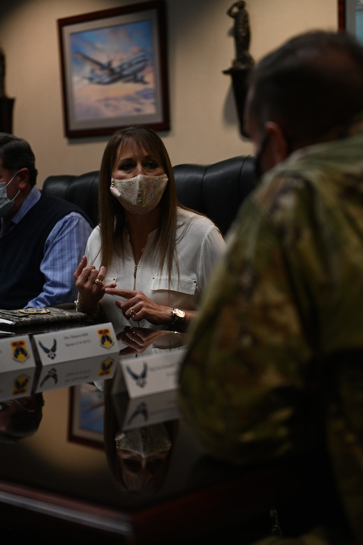 A woman in a mask stares into the camera during a briefing