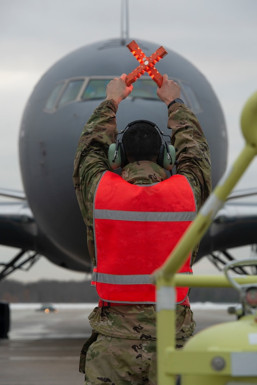 U.S. Air Force Tech. Sgt. Brandon Cevallos, a crew chief assigned to the 157th Air Refueling Wing, New Hampshire Air National Guard, marshalls in the 12th and final KC-46A Pegasus arrival at Pease Air National Guard Base, N.H., Feb. 5, 2021.