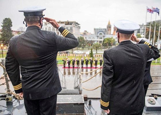 Cmdr. Matthew Curnen, commanding officer of the Arleigh Burke-class guided-missile destroyer USS Donald Cook (DDG 75), left, and Cmdr. Kurt Astroth, executive officer, salute as the American and Georgian national anthems are played during a ceremony in Batumi, Georgia, Feb. 5, 2021.