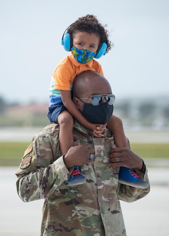 Master Sgt. Marcus Hawkins, 36th Munitions Squadron first sergeant, holds his son on his shoulders during a group flight line engagement for Exercise Cope North 2021 at Andersen Air Force Base, Guam, Feb. 5, 2021. Exercise Cope North 2021 is an annual U.S. Pacific Air Forces joint/combined, trilateral field training exercise occurring Feb. 3-19, 2021. (U.S. Air Force photo by Senior Airman Aubree Owens)