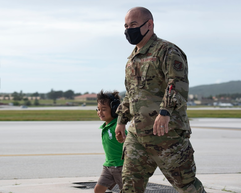 Maj. Elkin Medina 36th Expeditionary Aircraft Maintenance Squadron commander, walks with a fellow Airman's child during a group flight line engagement for Exercise Cope North 2021 at Andersen Air Force Base, Guam, Feb. 5, 2021. Exercise Cope North 2021 is an annual U.S. Pacific Air Forces joint/combined, trilateral field training exercise occurring Feb. 3-19, 2021. (U.S. Air Force photo by Senior Airman Aubree Owens)