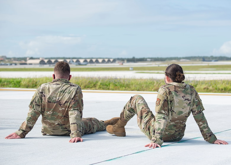 Two Airmen assigned to the 36th Maintenance Group watch aircraft take off during a group flight line engagement for Exercise Cope North 2021 at Andersen Air Force Base, Guam, Feb. 5, 2021. Exercise Cope North 2021 is an annual U.S. Pacific Air Forces joint/combined, trilateral field training exercise occurring Feb. 3-19, 2021. The exercise includes participants from the U.S. Air Force, U.S. Navy, U.S. Marine Corps, Japan Air Self-Defense Force and Royal Australian Air Force. (U.S. Air Force photo by Senior Airman Aubree Owens)