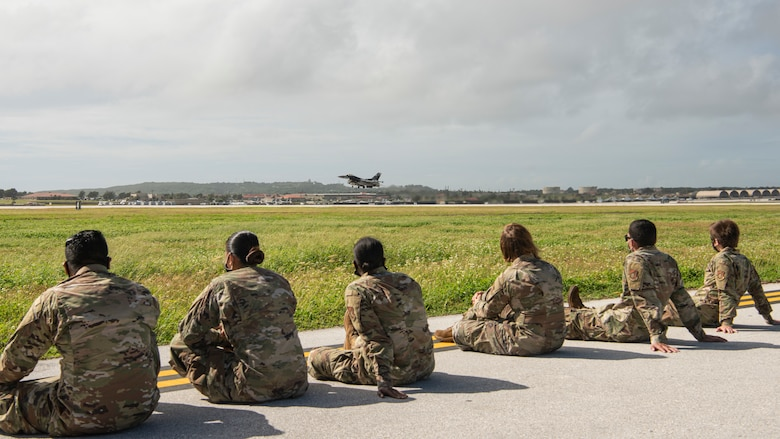 Airmen assigned to the 36th Maintenance Group watch as a U.S. Air Force F-16 Fighting Falcon, assigned to the 18th Aggressor Squadron, Eielson Air Force Base, Alaska, takes off during a group flight line engagement for Exercise Cope North 2021 at Andersen AFB, Guam, Feb. 5, 2021. Exercise Cope North 2021 is an annual U.S. Pacific Air Forces joint/combined, trilateral field training exercise occurring Feb. 3-19, 2021. The exercise includes participants from the U.S. Air Force, U.S. Navy, U.S. Marine Corps, Japan Air Self-Defense Force and Royal Australian Air Force. (U.S. Air Force photo by Senior Airman Aubree Owens)