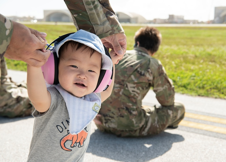 Maj. Timothy Wu holds his son's hands while they watch aircraft take off during a group flight line engagement for Exercise Cope North 2021 at Andersen Air Force Base, Guam, Feb. 5, 2021. Exercise Cope North 2021is an annual U.S. Pacific Air Forces joint/combined, trilateral field training exercise occurring Feb. 3-19, 2021. (U.S. Air Force photo by Senior Airman Aubree Owens)
