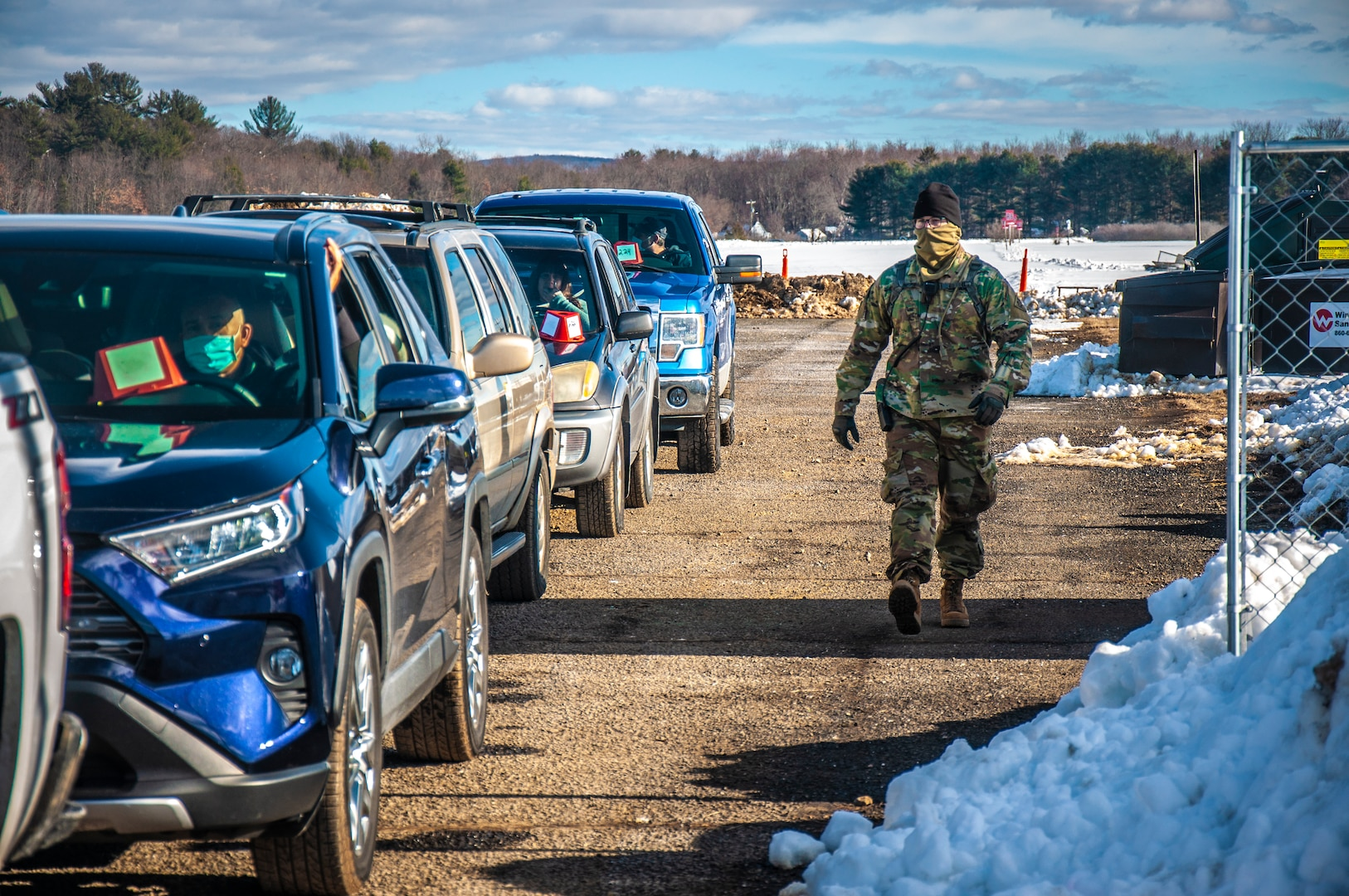 Staff Sgt. Ryan Gilbert, a combat engineer from the Connecticut National Guard's 192nd Engineer Battalion, walks down a line of cars to check on the passengers after receiving the COVID-19 vaccination at Rentschler Field in East Hartford, Jan. 4, 2021.