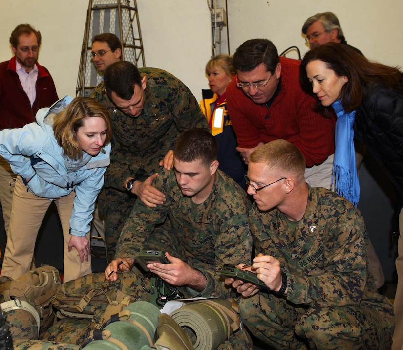 Three civilians lean over to look at a small device being held in the hand of a service member as other service members watch.