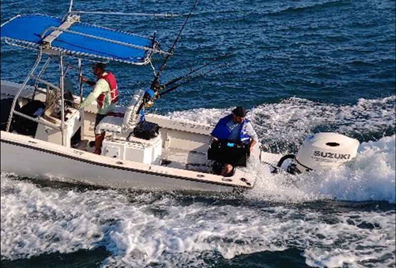 The crew of a distressed boat uses a trash can to dump water from their small boat taking on water off the coast of