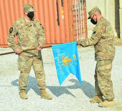 Lt. Col. Jason Osberg, of Champaign, Illinois, Commander Bilateral Embedded Support Team A25, and Master Sgt. Adam Abdul, of Collinsville, Illinois, prepare to case the BEST A colors during the decommissioning ceremony at Bagram Airfield, Afghanistan.