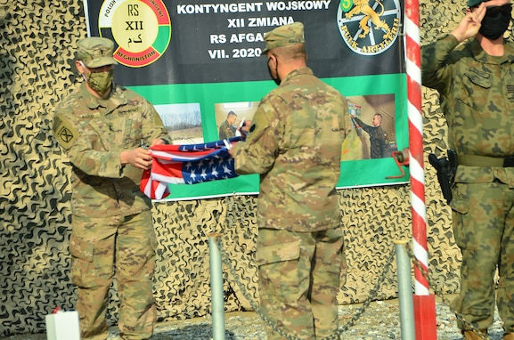 1st Lt. Kurt Kuzur, of Tinley Park, Illinois and Master Sgt. Adam Abdul, of Collinsville, Illinois, fold the U.S. flag during the Illinois Army National Guard Bilateral Embedded Staff Team (BEST) A25 decommissioning ceremony at Bagram Airfield, Afghanistan.
