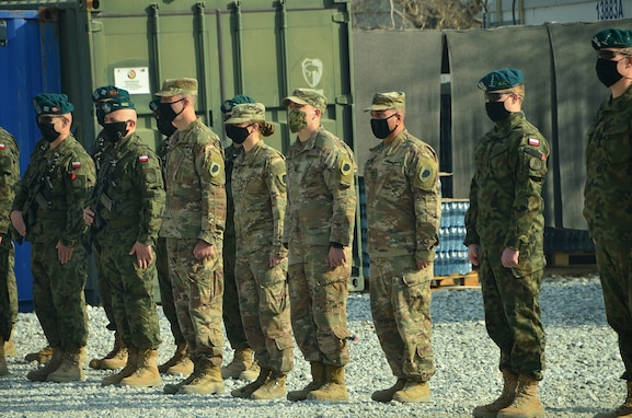 The Illinois Army National Guard Bilateral Embedded Support Team (BEST) A25 stand alongside the Polish military contingent during the ILARNG BEST decommissioning ceremony at Bagram Airfield, Afghanistan. Soldiers deployed with BEST A25 returned home Dec. 24.