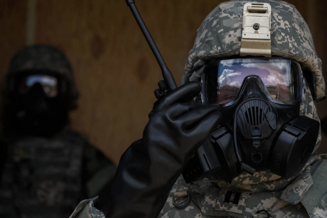 Service member performs training exercise to practice wearing CBRN protective gear.