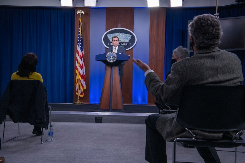 A man at a lectern answers questions from an audience of reporters.. A sign indicating that he is at the Pentagon is behind him.